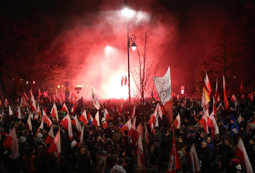Poles marking Independence Day carry flags and burning flares during a march through Warsaw on Monday night that news agencies estimate drew as many as 50,000. A mob of nationalist youths later broke away and attacked the Russian Embassy.