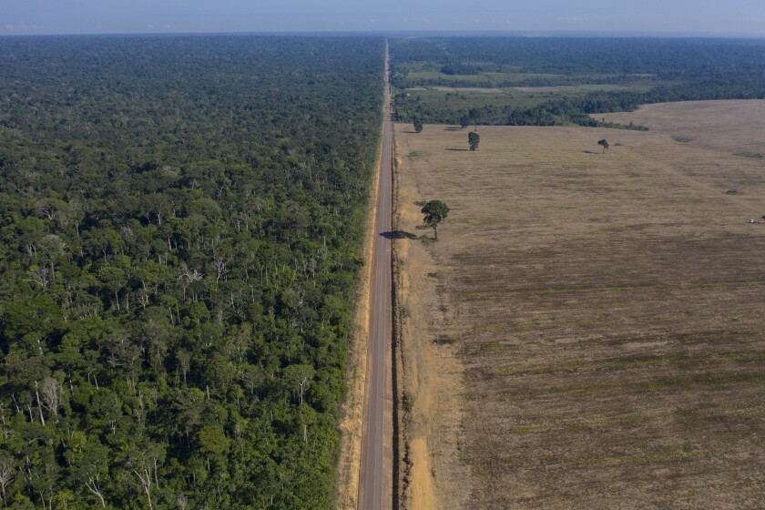 FILE - In this Nov. 25, 2019 file photo, highway BR-163 stretches between the Tapajos National Forest, left, and a soy field in Belterra, Para state, Brazil. At the U.S.-led climate summit on April 22, 2021, Brazil's President Jair Bolsonaro shifted his tone on Amazon preservation and exhibited willingness to step up commitment, even though many critics remain doubtful of his credibility. (AP Photo/Leo Correa, File)