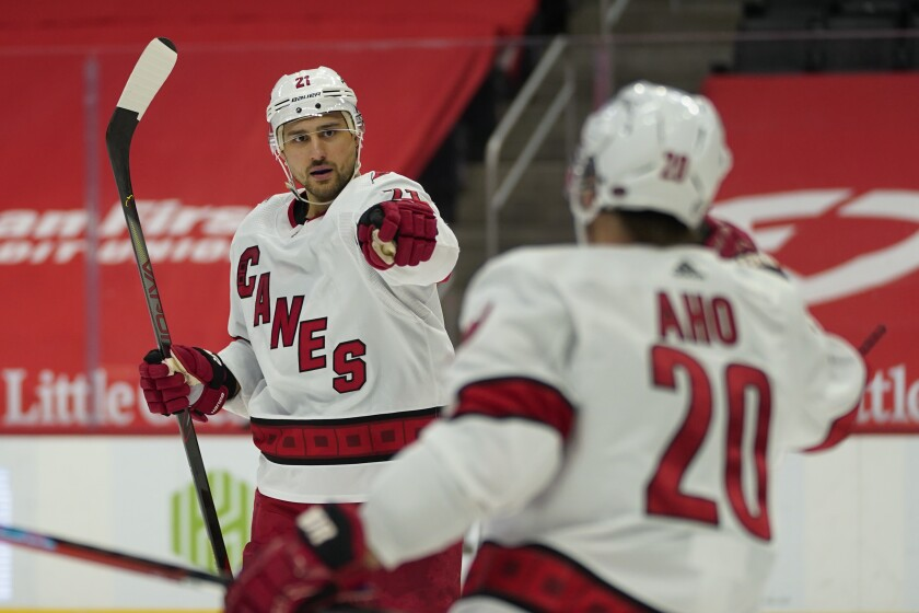 Carolina Hurricanes right wing Nino Niederreiter (21) celebrates his goal with Sebastian Aho (20) in the third period of an NHL hockey game against the Detroit Red Wings, Sunday, March 14, 2021, in Detroit. (AP Photo/Paul Sancya)