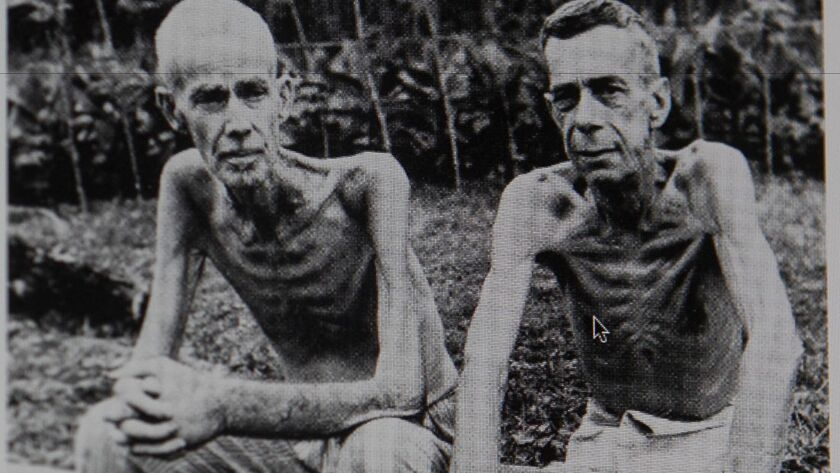 After the Santo Tomas Internment camp in Manila was liberated, two emaciated former internees sat, waiting to be let out of the camp.