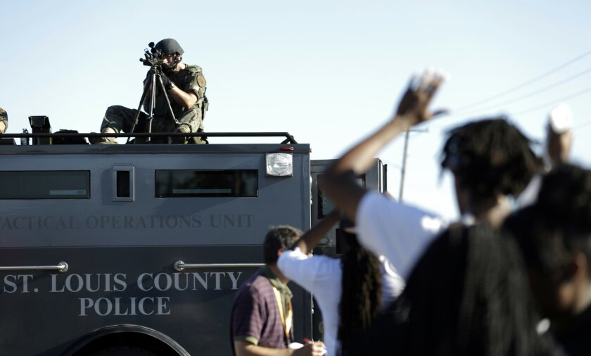 A member of the St. Louis County Police Department points his weapon in the direction of a group of protesters in Ferguson, Mo. on Wednesday, Aug. 13, 2014. On Saturday, Aug. 9, 2014, a white police officer fatally shot Michael Brown, an unarmed black teenager, in the St. Louis suburb. (AP Photo/Je