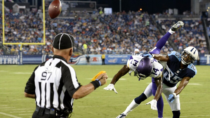 Side judge Tom Hill, left, throws a penalty flag as Titans cornerback Blidi Wreh-Wilson (25) breaks up a pass intended for Vikings wide receiver Stefon Diggs (14) in a preseason game on Sept. 3.