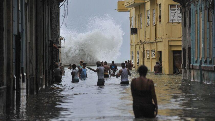 Cubans wade through a flooded street in Havana on Sept. 10, 2017.