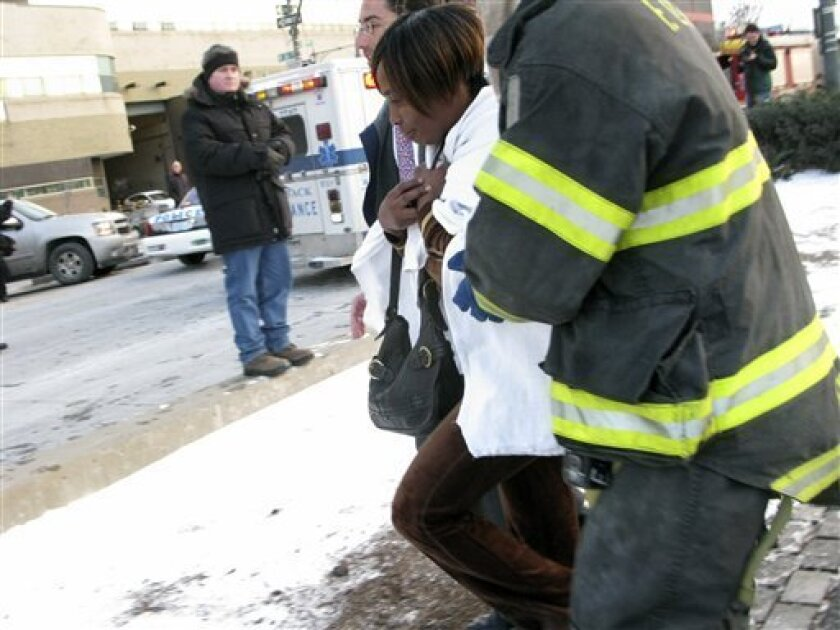 Authorities move an unidentified passenger, second from right, to a waiting ambulance after the plane she was on crashed into the Hudson River, Thursday, Jan. 15, 2009, in New York. A US Airways plane crashed into the frigid Hudson River on Thursday afternoon after striking a bird that disabled two