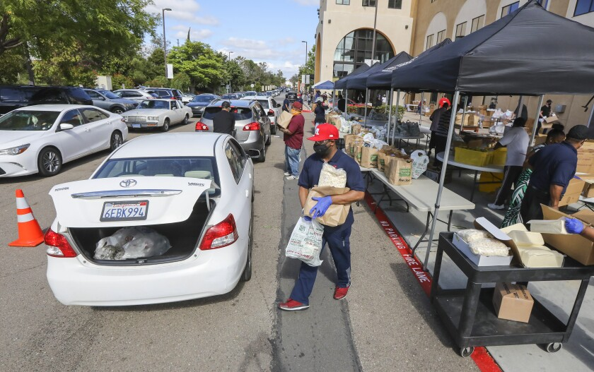 Charles Muhammad, who is from the I Am My Brothers Keeper organization, volunteers at the weekly food distribution event at the Jacobs Center for Neighborhood Innovation on May 12, 2020 in San Diego, California.