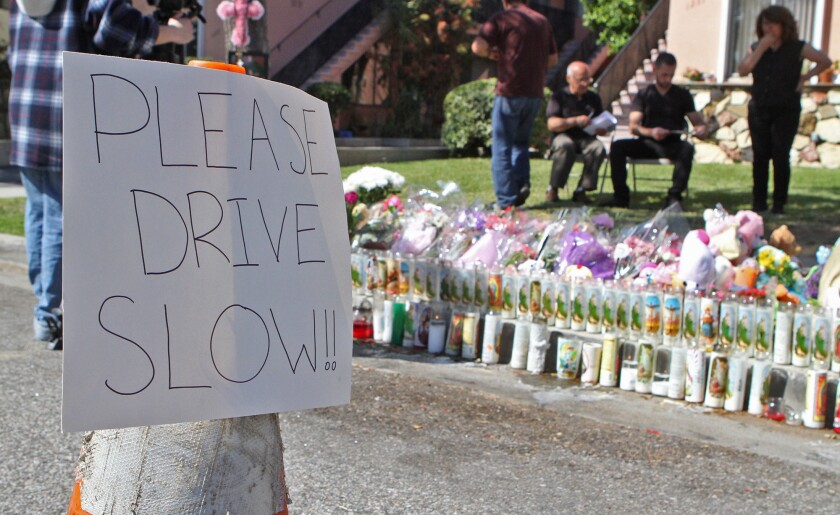 A sign warning drivers to slow down is placed next to the memorial site for 4-year-old Violeta Khachatoorians in Glendale on Monday, March 9, 2015. Three days prior, Violeta was killed by a hit-and-run driver, who eventually turned himself in.