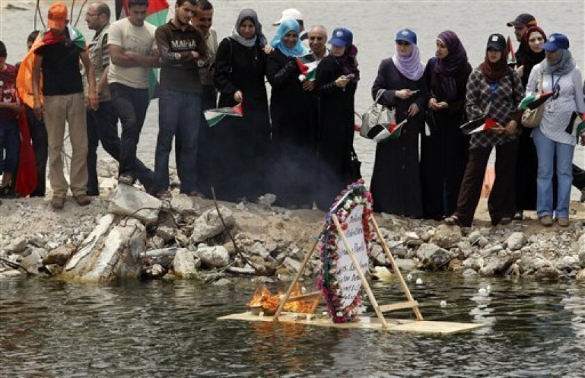 Palestinians look at a floating memorial sign during a protest against the Israeli naval commando raid on a flotilla attempting to break the blockade on Gaza, at the port in Gaza City, Tuesday, June 1, 2010. Palestinians in Gaza declared a general strike and a day of wrath following Israel's deadly