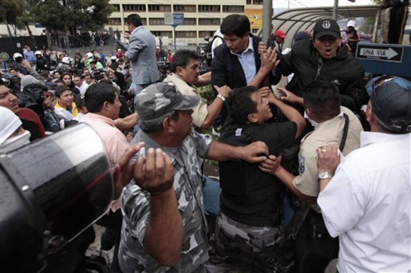 Lawmaker Cesar Rodriguez from the Alianza Pais party, second from top right, is blocked by protesting police from entering a hospital where Ecuador's President Rafael Correa is located in Quito, Ecuador, Thursday Sept. 30, 2010.  Hundreds of police are protesting a new law that cuts their benefits,