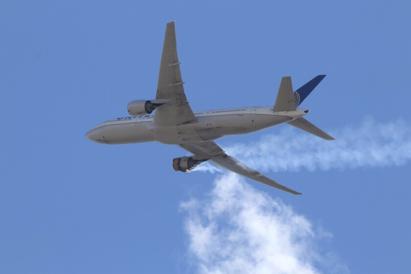 An airplane with a burning engine flies toward the Denver airport.