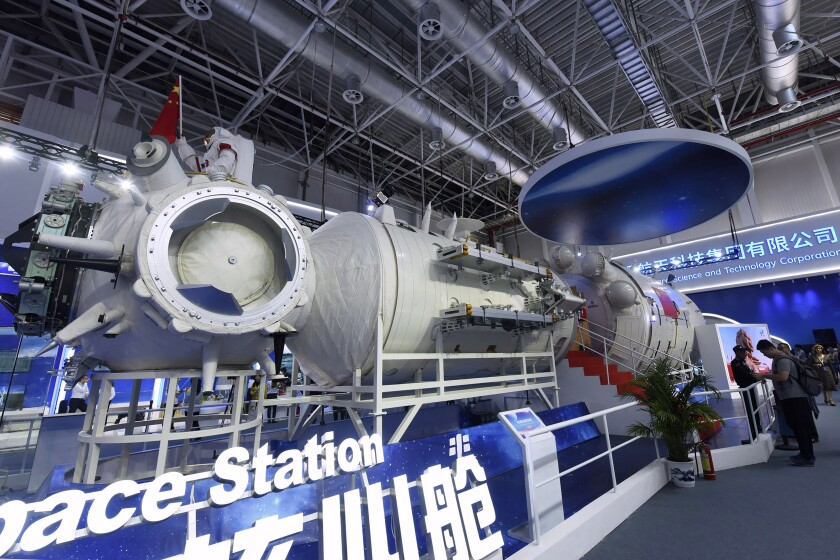 In this Nov. 7, 2018, photo, visitors look at a life-size model of the Tianhe core module of China's next space station at the Airshow China in Zhuhai in southern China's Guangdong Province. China on Thursday, June 17, 2021 has launched its first crewed space mission in five years, sending three astronauts to a new space station that marks a milestone in the country's ambitious space program. (Chinatopix via AP)