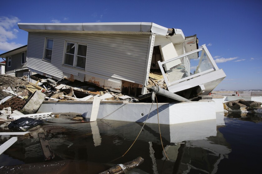 FILE - In this Thursday, Jan. 31, 2013 file photo, a storm-damaged beachfront house is reflected in a pool of water in the Far Rockaways, in the Queens borough of New York. A study released in the journal Nature Communications on Tuesday, May 18, 2021, says climate change added $8 billion to the massive costs of 2012's Superstorm Sandy. (AP Photo/Mark Lennihan, File)