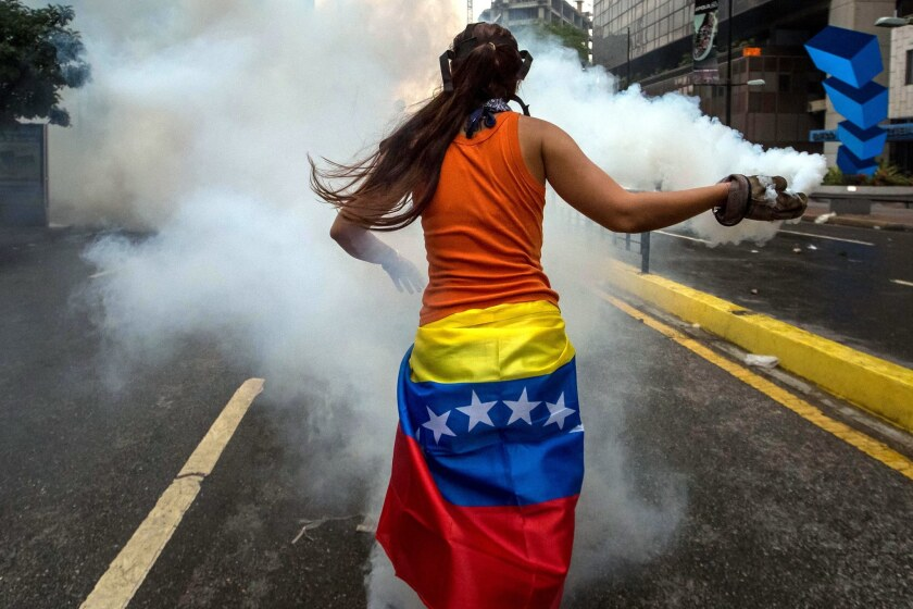 Demonstrators clash with police during an April protest in Caracas, Venezuela. Oil is estimated to a