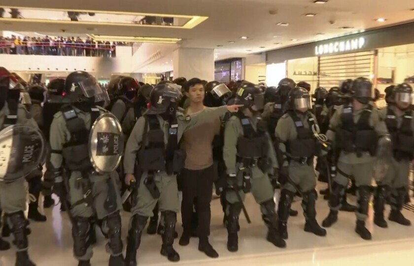 In this image made from video, a protester is arrested by police at a shopping mall in Sha Tin district in Hong Kong, while shoppers watch from balconies above Sunday.