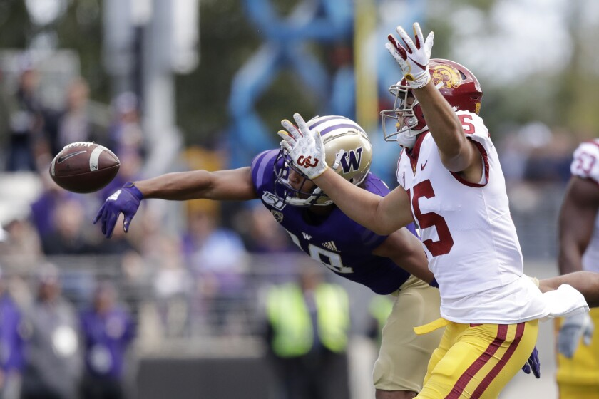 Washington's Kyler Gordon, left, knocks away a pass intended for USC's Drake London in the first half on Saturday in Seattle.