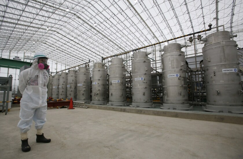 A Tokyo Electric Power Co. official stands in front of Advanced Liquid Processing Systems at the Fukushima Dai-ichi nuclear power plant.