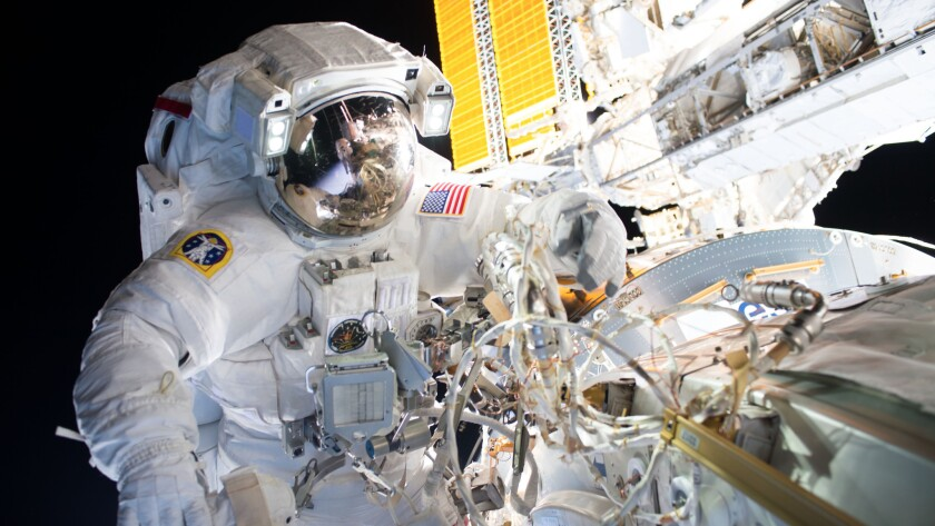 A NASA astronaut installs international docking adapters on the International Space Station.