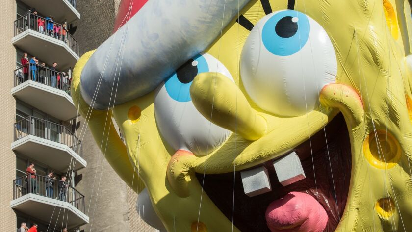 Spectators watch as the balloon of Spongebob Squarepants is moved down Central Park West during the