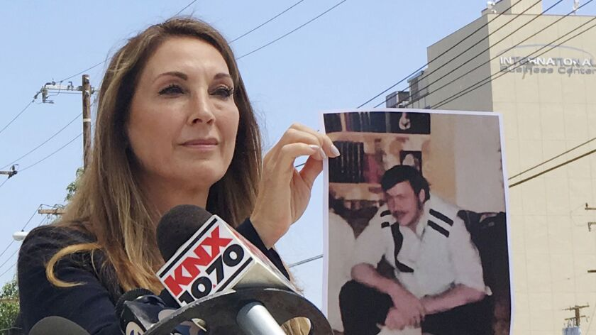 Attorney Annee Della Donna holds a photo of the late William Evins, who was convicted in the slaying of a woman in 1979, outside Superior Court in Santa Ana on Wednesday.