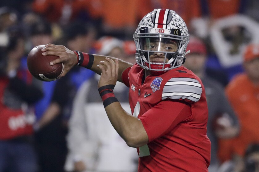 """FILE - In this Dec. 28, 2019, file photo, Ohio State quarterback Justin Fields throws a pass against Clemson during the first half of the Fiesta Bowl NCAA college football playoff semifinal in Glendale, Ariz. When Fields got together with some of his teammates last Saturday to watch college football on TV, the mood was dark. """"Distraught,"""" Fields said. (AP Photo/Rick Scuteri, File)"""