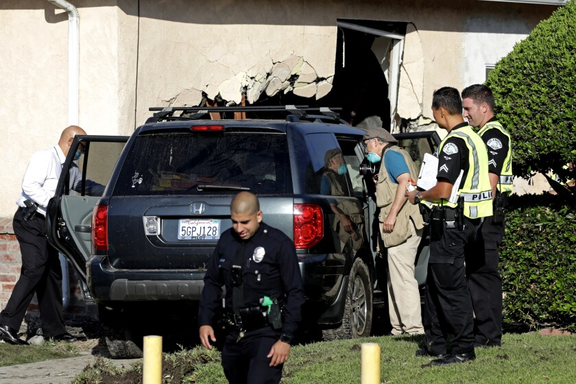 Police investigate the scene where an SUV crashed into a home