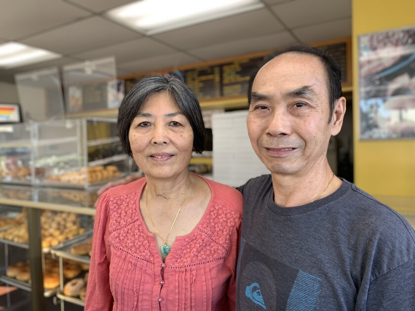 Stella and John Chhan at their shop, Donut City, in Seal Beach. A year ago, they were the subject of a viral story when Stella had a brain aneurysm and locals bought out the store's donuts so John could close up shop early and visit his wife every day. Now, she's back behind the counter.
