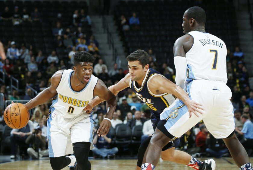 Denver Nuggets guard Emmanuel Mudiay, left, drives to shoot past Utah Jazz guard Raul Neto, center, of Brazil, as he fights through a pick set by Nuggets forward J.J. Hickson in the first half of an NBA basketball game Thursday, Nov. 5, 2015, in Denver. (AP Photo/David Zalubowski)