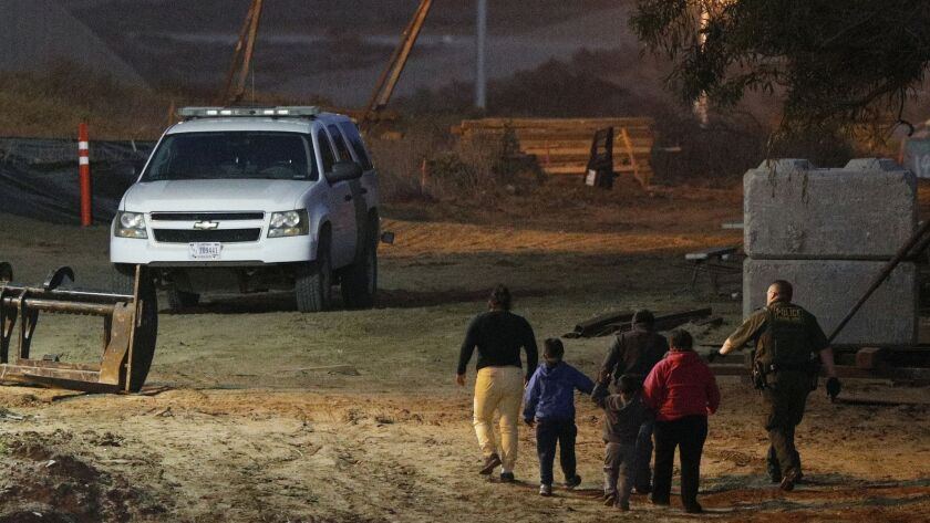 FILE - In this Dec. 3, 2018, file photo, migrants are escorted by a U.S. Border Patrol agent as they