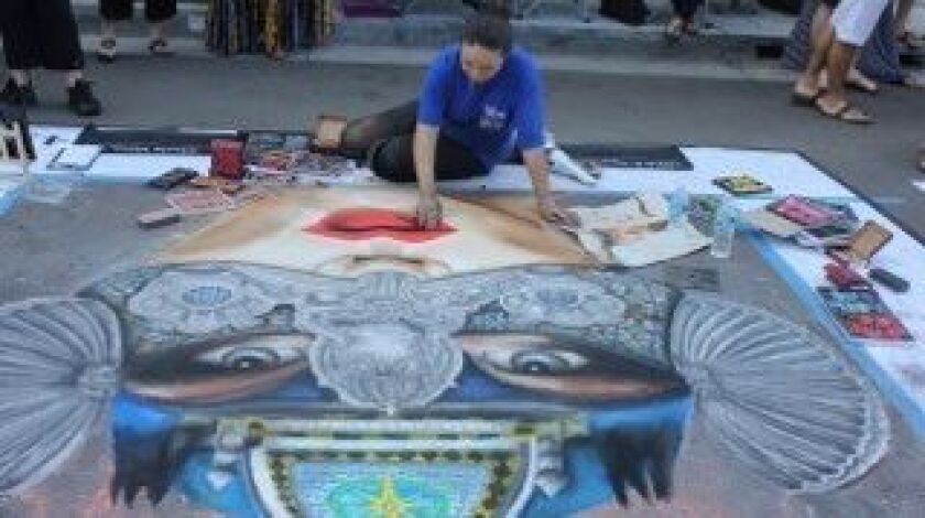 Lidia Vazquez works on her Balboa-themed chalk art for the centennial last year.