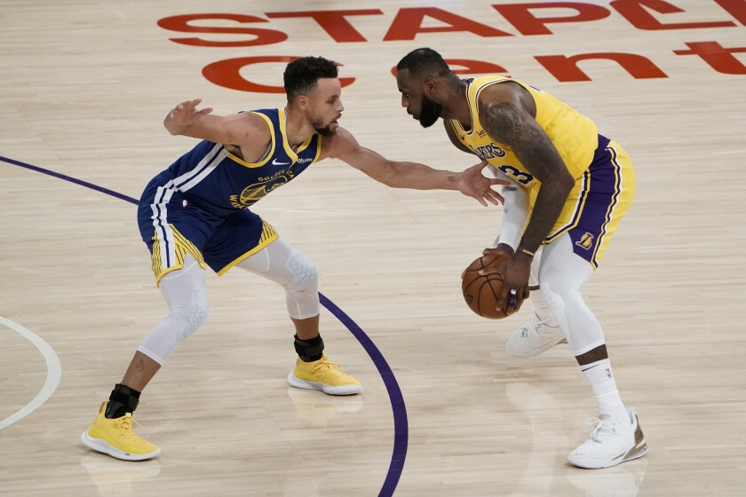 Lakers forward LeBron James looks to drive against Warriors guard Stephen Curry.