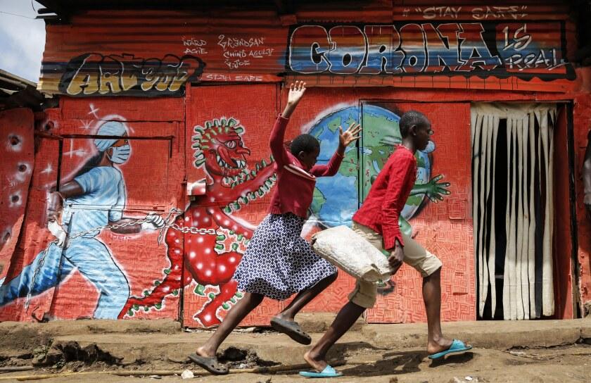 ARCHIVO - En esta imagen del miércoles 3 de junio de 2020, niños corriendo por una calle pasan junto a un cartel informativo alertando sobre los riesgos del nuevo coronavirus, en la barriada de Kibera, en Nairobi, Kenia. (AP Foto/Brian Inganga, Archivo)