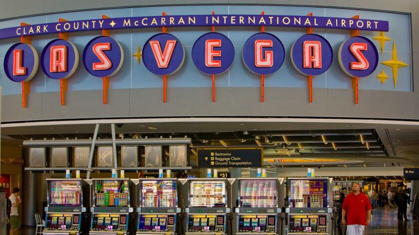 Slot machines beckon travelers at McCarran International Airport. (George Rose / Getty Images)