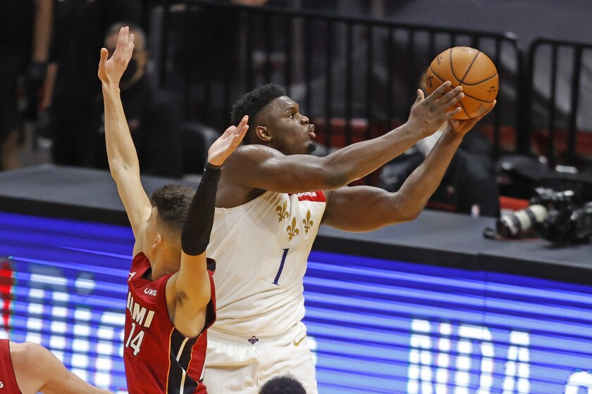 Pelicans forward Zion Williamson gets past Heat guard Tyler Herro for a layup during the second half on Dec. 25, 2020.