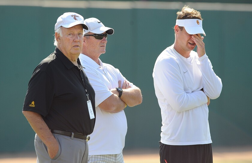 Former USC coach John Robinson, left, watches a USC practice session with ex-Cal coach Jeff Tedford, center, and ex-USC coach Lane Kiffin.