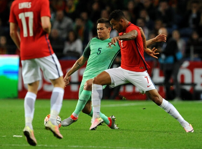 Portugal's Raphael Guerreiro, centre, challenges Norway's Joshua King during a friendly soccer match between Portugal and Norway at the Dragao stadium in Porto, Portugal, Sunday, May 29, 2016. The Portuguese squad is in preparation for the UEFA EURO 2016 soccer championships, hosted by France. (AP