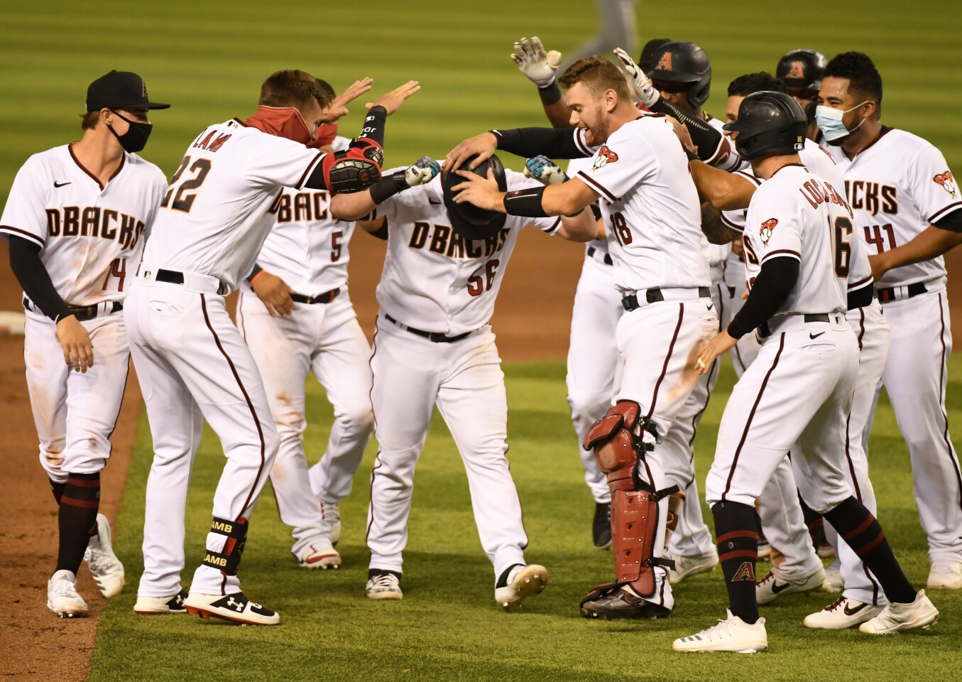 PHOENIX, ARIZONA - AUGUST 06: Kole Calhoun #56 of the Arizona Diamondbacks celebrates with Carson Kelly #18, Jake Lamb #22 and teammates after hitting a walk off two run single during the ninth inning for a 5-4 win against the Houston Astros at Chase Field on August 06, 2020 in Phoenix, Arizona. (Photo by Norm Hall/Getty Images)
