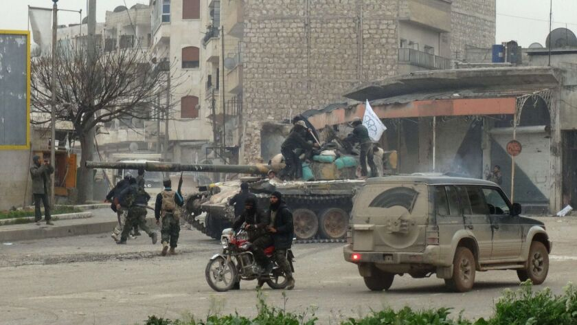 Fighters loyal to Al Nusra Front and its allies gather around a tank on a square in the northwestern Syrian city of Idlib on March 28, 2015.