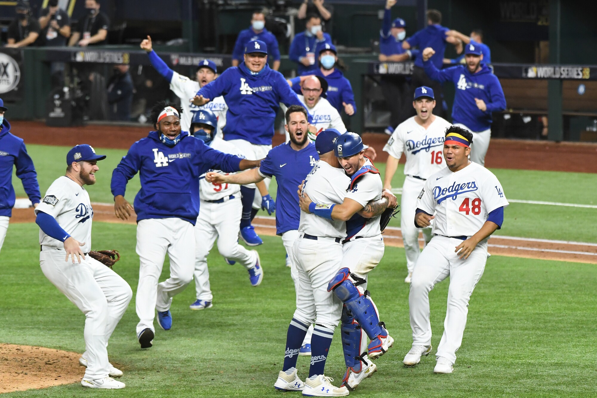 Dodgers embrace on the field as they celebrate their World Series win.