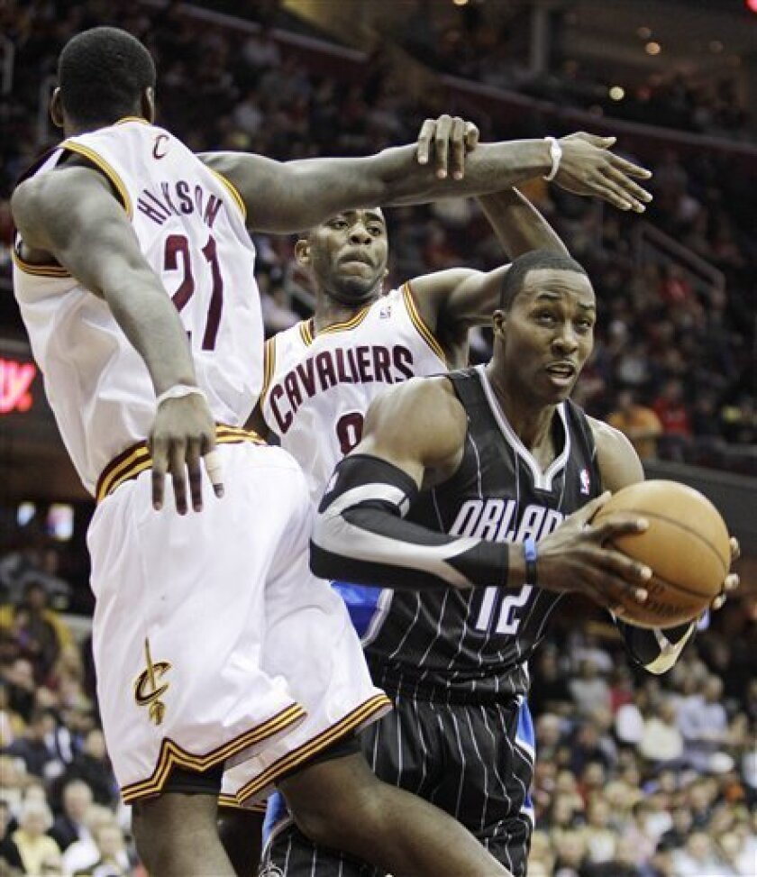 Orlando Magic's Dwight Howard (12) squeezes between Cleveland Cavaliers' J.J. Hickson (21) and Christian Eyenga, from Congo (8) in the second quarter in an NBA basketball game, Monday, March 21, 2011, in Cleveland. (AP Photo/Tony Dejak)
