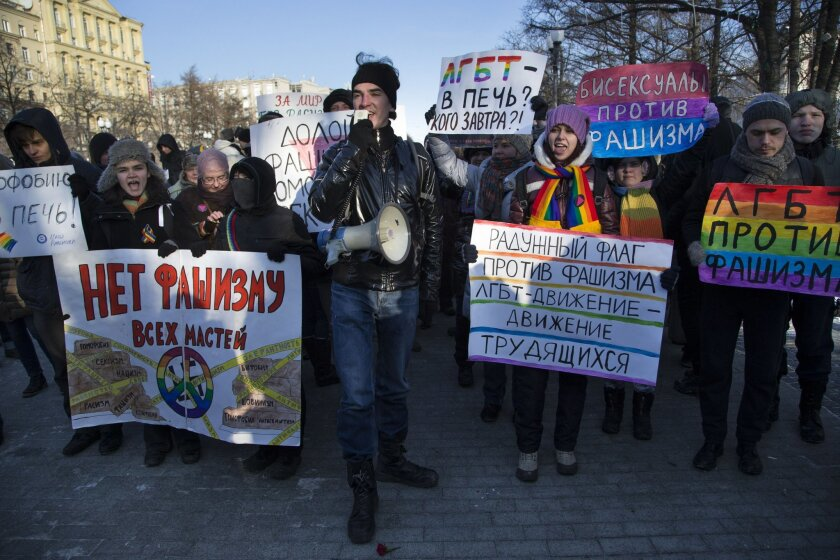 FILE - In this Sunday, Jan. 19, 2014 file photo Russian gay rights activists march along a Moscow boulevard in downtown. Slogans read: ' Down with all Kinds of Fascism', ' Homophobia into the Fire!', ' For Peace without Racism ! ',  and 'Bisexuals Against Fascism'. When the Sochi Winter Olympics be