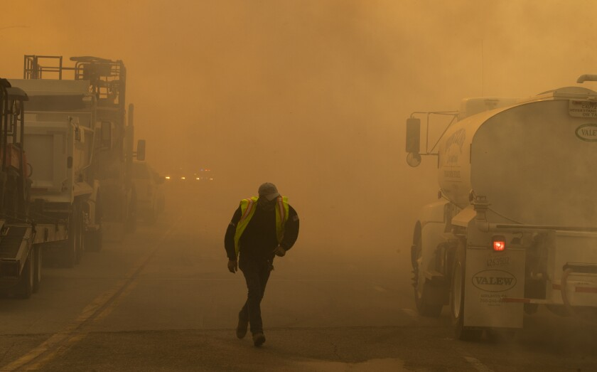 A water truck operator runs through the thick smoke of the advancing Silverado Fire fueled by Santa Ana winds at the 241.