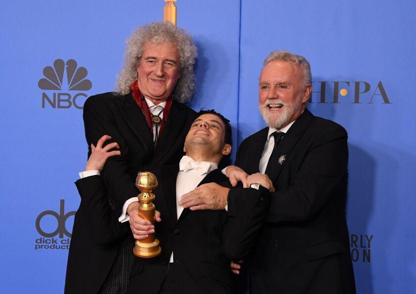 El actor Rami Malek posa con los miembros de Queen Roger Taylor (d) y Brian May (izq) tras ser premiado en los Globos de Oro.
