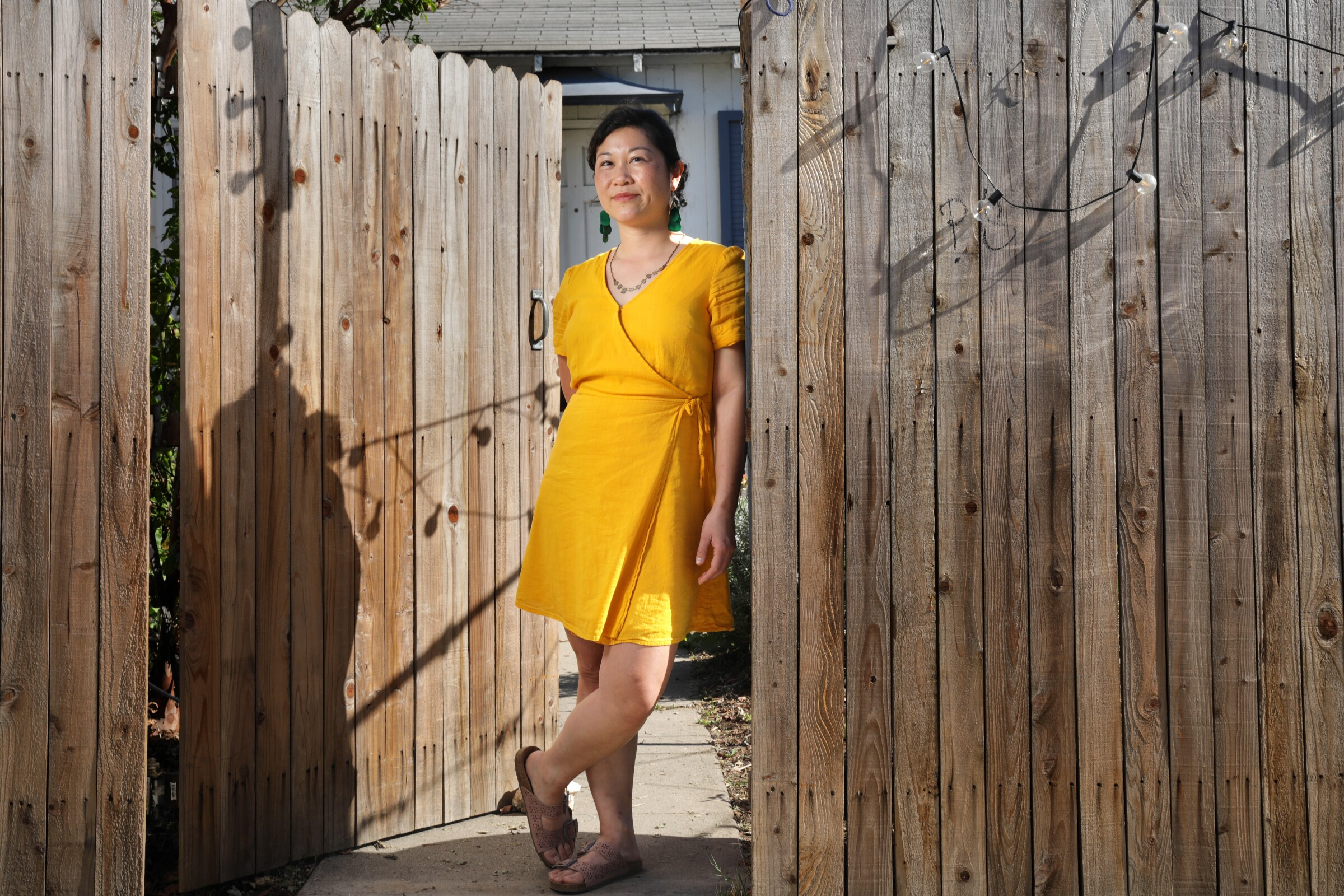 A woman leans against a wooden fence