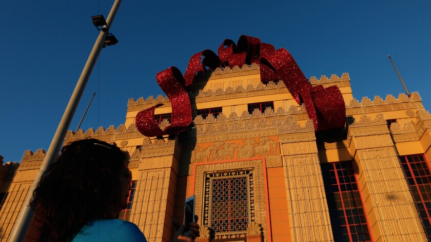 Is it that time already? A visitor snaps a photo beneath the Citadel Outlets' Christmas bow.