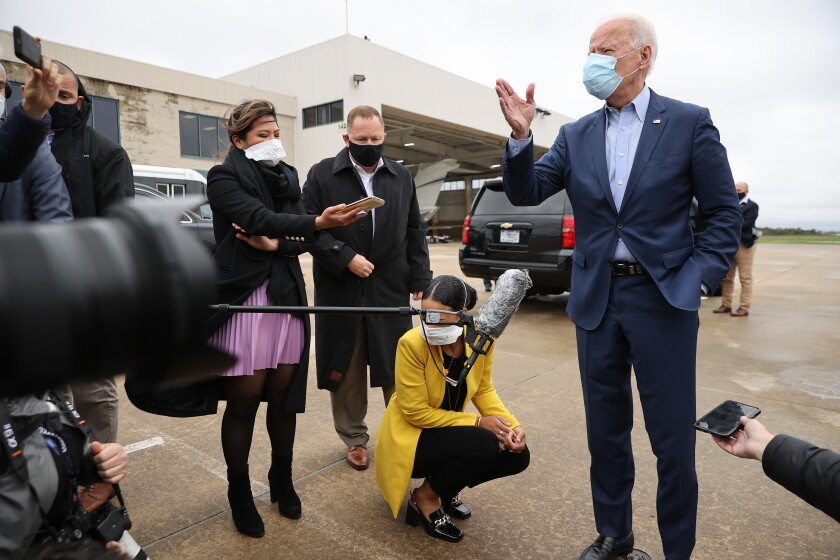 Joe Biden, masked, gestures as he talks with reporters outside a Delaware airport.