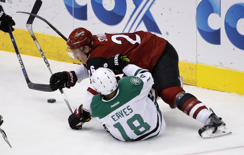 Arizona Coyotes' Michael Stone (26) sends Dallas Stars' Patrick Eaves (18) to the ice during the second period of an NHL hockey game Thursday, Feb. 18, 2016, in Glendale, Ariz. (AP Photo/Ross D. Franklin)