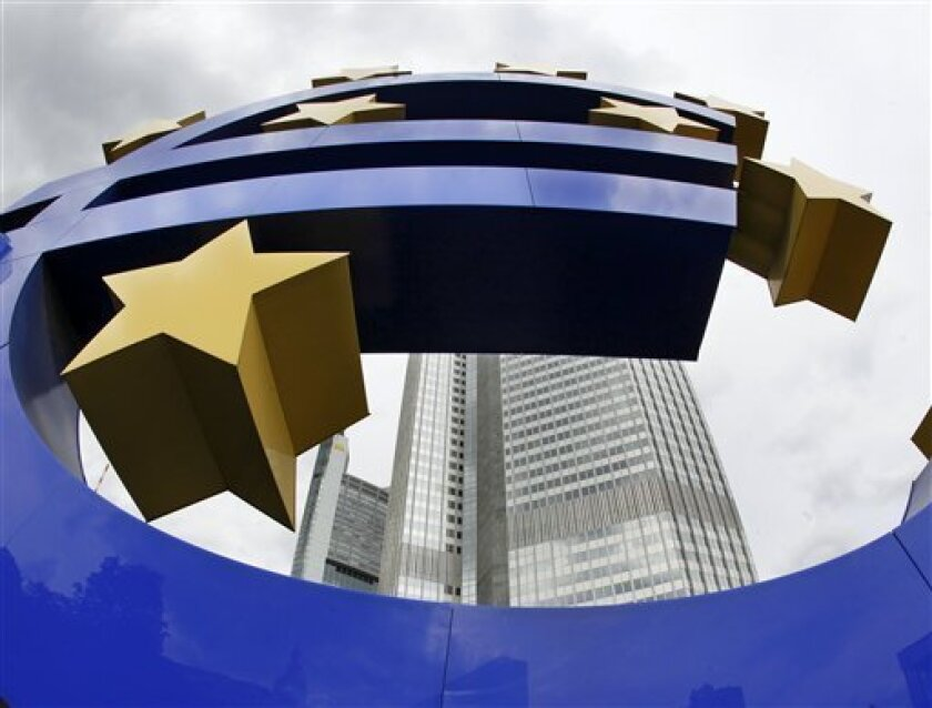 FILE - In this Sept. 2, 2009 file picture the Euro sculpture is photographed in front of the European Central Bank ECB in Frankfurt, central Germany. The European Central Bank raised its key interest rate by a quarter point Thursday April 7, 2011, underlining its determination to fight rising inflation even as several euro member countries struggle with ailing economies and a debt crisis. The refinancing rate was lifted to 1.25 percent from a record low of 1 percent, where it had been since May 2009, only a day after Portugal asked for an international bailout. The move highlights the dilemma facing the central bank as it tries to set a single monetary policy for a region that spans 17 different economies. (AP Photo/Michael Probst, File)