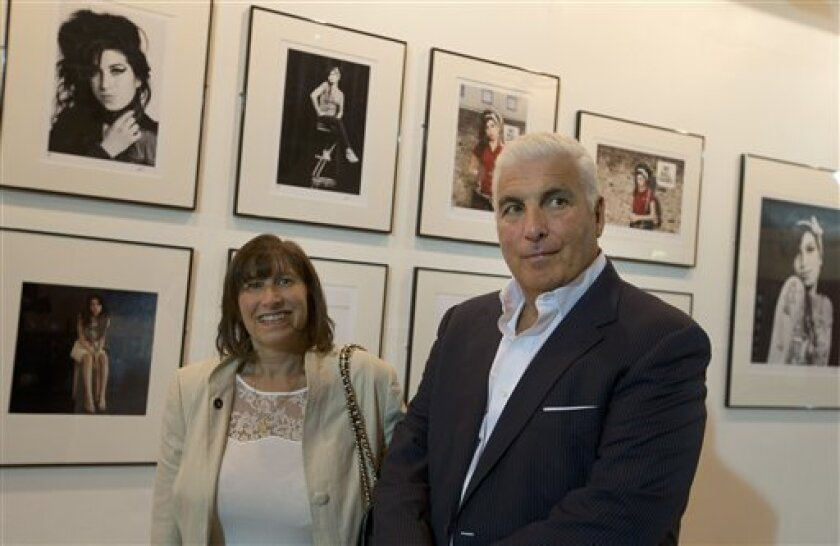 Janice and Mitch Winehouse mother and father of the late British singer Amy pose for the media, in front of portraits of their daughter at the Proud gallery in Camden, London, Wednesday, Sept.11, 2013. In the month she would have turned 30, Amy Winehouse is being celebrated in Camden the London neighbourhood that was her physical and spiritual home, she died of accidental alcohol poisoning at her house in July 2011, aged 27. The neighbourhood still attracts her fans, and local officials and bus