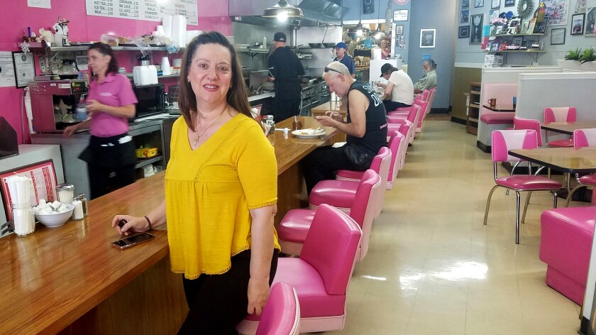 Vickie Kelesis, in a yellow top, stands at the pink-seated counter of her Vickie's Diner.