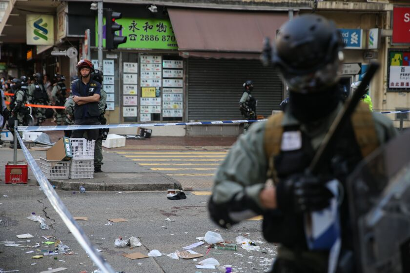 Police stand guard at an area in Hong Kong where a protester was shot by an officer.