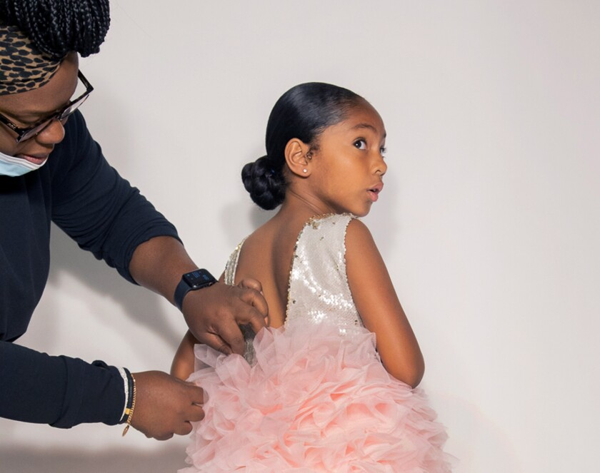 Michelle Youngblood, owner of Brooklynn & Blake, fits one of her designer dresses, called Modern Ballerina, on Ava Marie, 8.